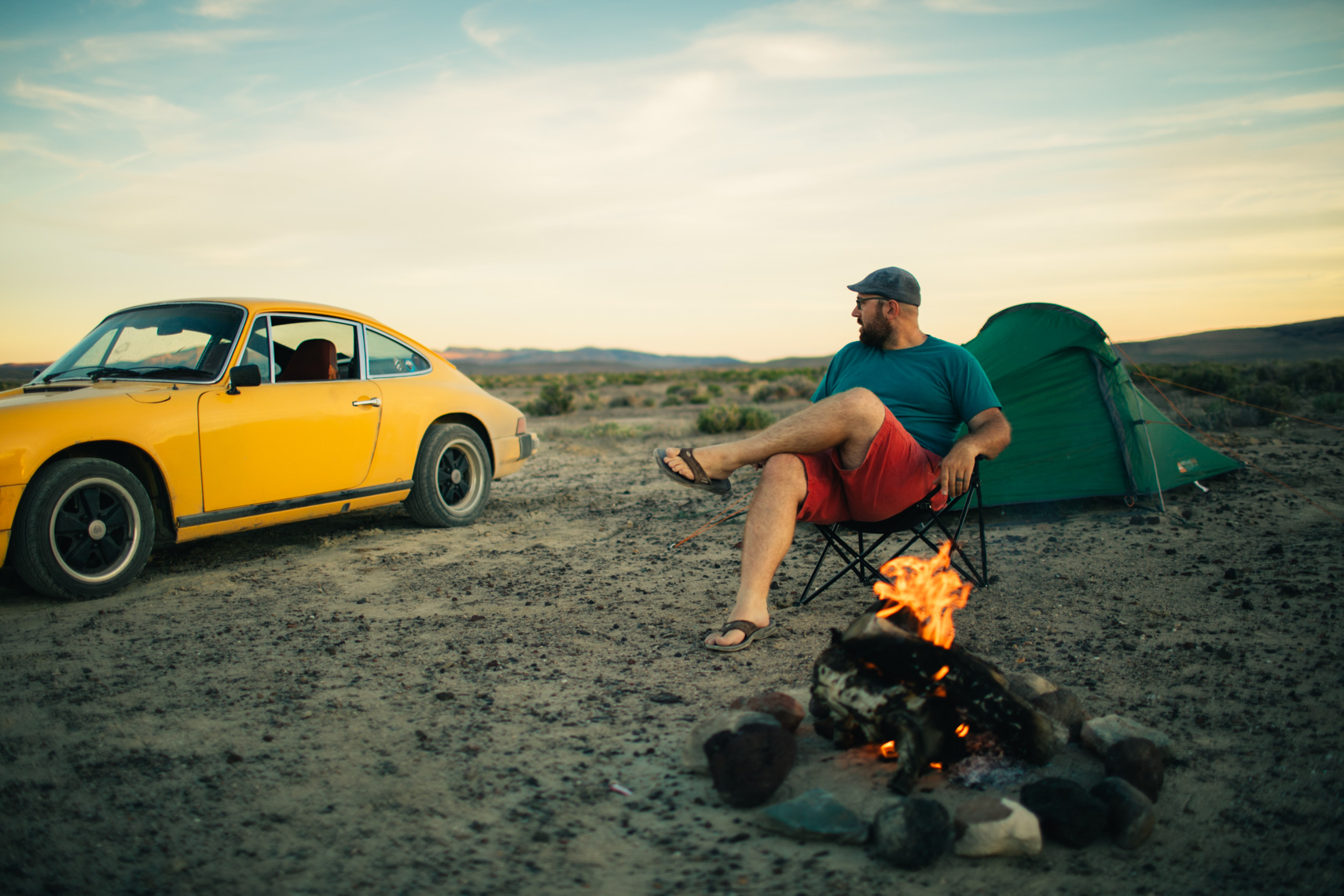 Man Relaxing In Desert with Porsche