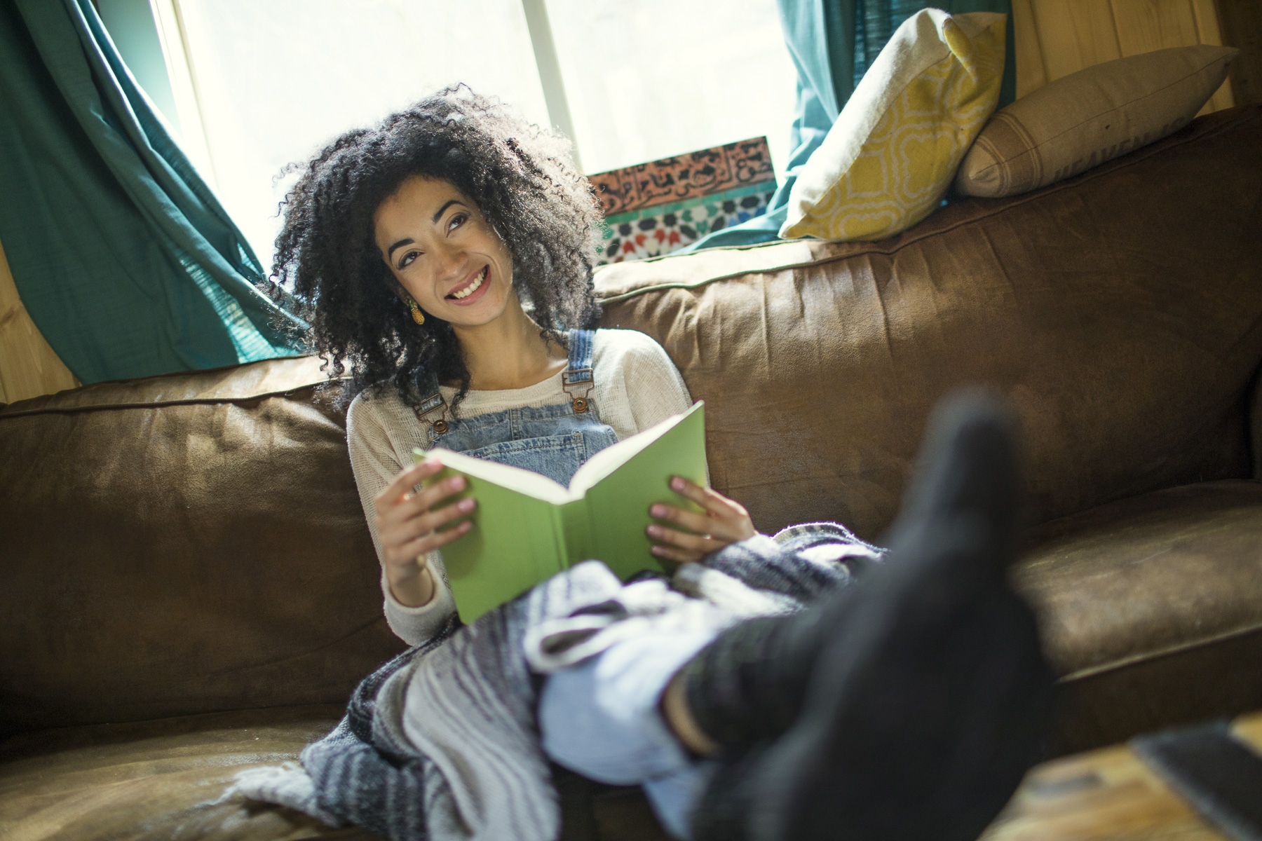 Young woman reading book in socks