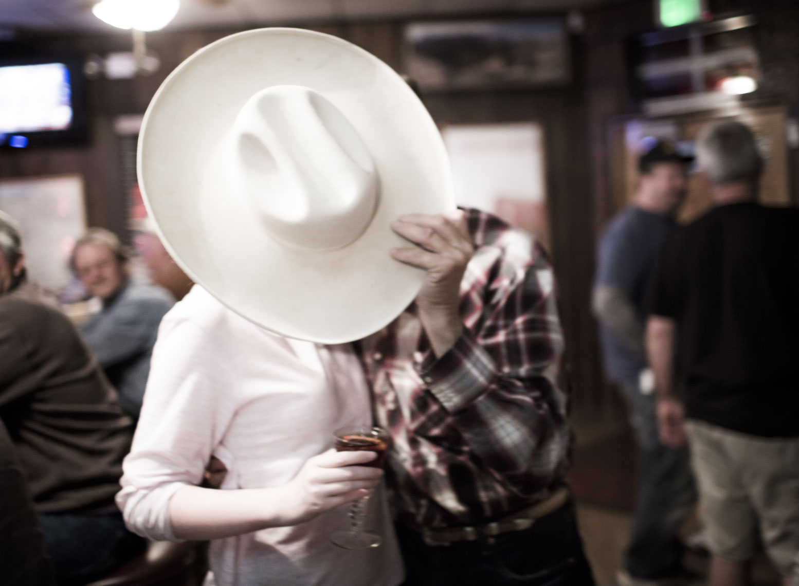 Man Kissing Girl Behind Cowboy Hat